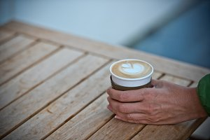 Female hand holding a paper coffee