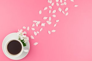 Flat lay of coffee and white flowers