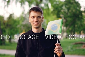 Slow motion portrait of glad traveller young man holding Brazilian flag and smiling looking at camera. National symbol, proud people, summertime and nature concept.