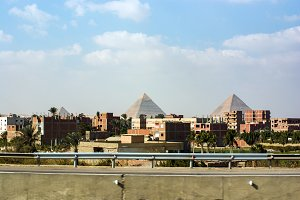 View of the pyramids of Keops, Kefren and Menkaure from the ring road of Cairo. Ahead half-built homes