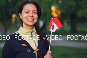 Slow motion portrait of attractive girl Canadian sports fan holding national flag of Canada and looking at camera with smile. People and countries concept.
