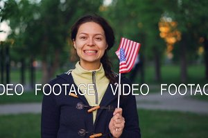 Slow motion portrait of pretty young lady American fan looking at camera and smiling waving flag of the United States. Happy people, countries and patriotism concept.