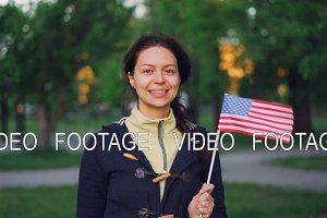 Slow motion portrait of proud American citizen smiling woman waving US flag, looking at camera and smiling. Green trees, lawns, paths in the park are visible.