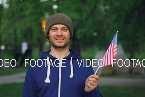 Slow motion portrait of bearded American guy proud citizen waving official US flag and looking at camera with glad smile. People, countries and landscapes concept.