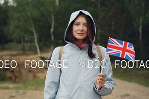 Slow motion portrait of charming Englishwoman holding flag of the Great Britain, smiling and looking at camera. Beautiful forest with green trees in background, windy spring day.