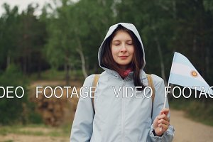 Slow motion portrait of female world traveller holding Argentinian flag flying in the wind, smiling and looking at camera. Beautiful green forest is in background.