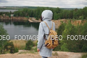 Slow motion portrait of young woman tourist with backpack walking to the edge of cliff with beautiful view of lake and forest. Travelling, people and nature concept.