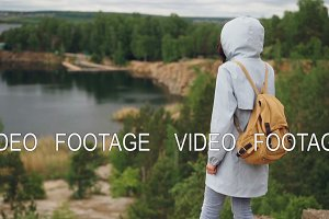 Tilt-down slowmotion portrait of slender girl walking on the cliff with her back to camera and watching beautiful landscape with lake and trees beneath her.