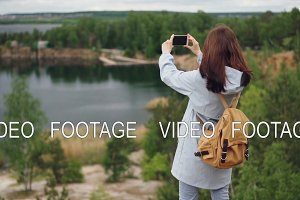 Slow motion portrait of girl traveller with knapsack taking pictures of beautiful view from cliff using smartphone. Beautiful blue lakes and green forests are visible.
