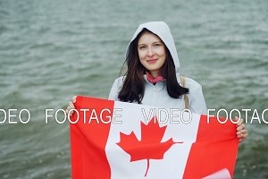 Slow motion portrait of cheerful young lady proud citizen holding fluttering Canadian flag and smiling looking at camera standing near the ocean.