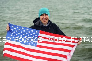 Slow motion portrait of cheerful traveller holding American national flag in hands and moving it celebrating freedom. Beautiful ocean waves are visible in background.
