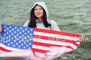 Slow motion portrait of happy American girl holding United States flag and moving it standing on the sea coast with waves visible. Nationality and countries concept.