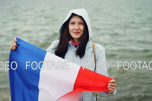 Slow motion portrait of cheerful French patriot holding official flag of France with cute smile standing near the water and smiling. Nationalism and youth concept.