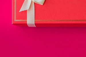 Red gift box on a bright scarlet bac