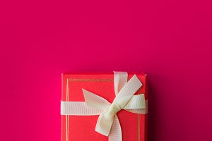 Red gift box on a bright scarlet