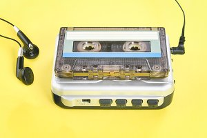 A cassette music player with a cassette and headphones on a yellow pastel background.
