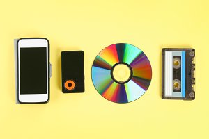 The concept of the evolution of music. Cassette, CD-disk, mp3 player, mobile phone. Vintage and modernity. Music support.
