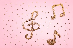 Musical notes of starry golden confetti lying on a pink pastel background.
