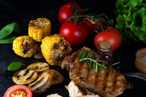 Grilled pork steak and vegetable , baked potatoes and green salad on dark