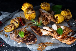 chopped chicken meat, pork and beef with corn, spices on paper on a dark background