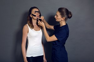 girl cosmetologist glues the clans in the face of a woman standing
