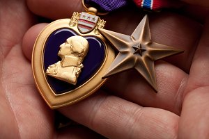 Man Holding Purple Heart and Bronze
