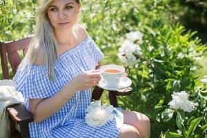 the girl is drinking tea in garden