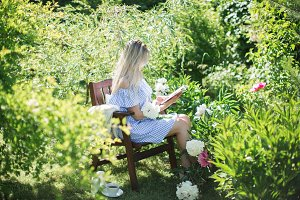 the girl is reading book in garden