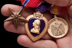Man Holding Purple Heart, Bronze and National Defense War Medals in The Palm of His Hand.
