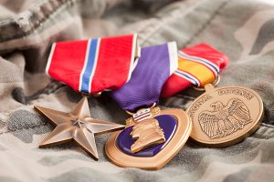 Bronze, Purple Heart and National Defense Medals on Camouflage Material.