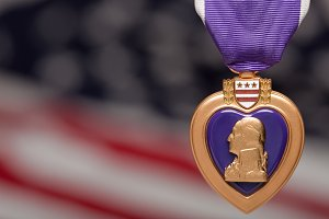 Purple Heart Against a Blurry American Flag.