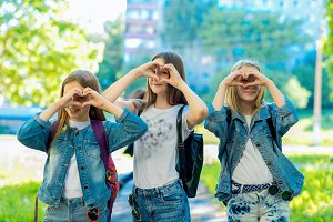 Three teenage girls. Summer in nature. Smile happily. In Stylish Denim Clothing. Hands gesture shows love. Concept kindness and positive. Emotions of happiness and friendship. Rest after school.