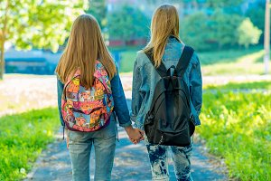 Two girl friends schoolgirl. Summer in nature. Girls hold each other's hands. Back view. Returns home after school. The concept of friendship. Walk in park.