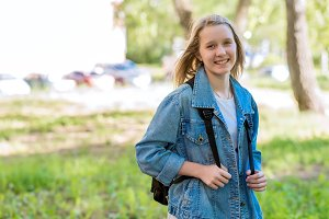 A teenage girl in summer in park. Smiling happily after school. In nature behind the backpack. Free space for text.