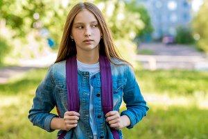 Beautiful schoolgirl girl. Summer in nature. Rest in city behind the backpack. Looking away. Returned after school.