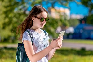 Beautiful brunette girl. In the summer in park. In his hands holds a smartphone. Writes messages on social networks. In a white T-shirt and sunglasses. Rest after school.