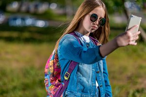 Girl schoolgirl in summer in park after school. In his hands holds a smartphone. Gestures communication on a mobile video call. Dressed in jeans clothes with sunglasses. Outdoors.