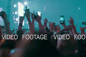 Crowded concert hall, fans dancing and making videos with cells