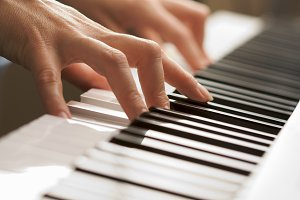 Woman's Hands Playing Piano Keyboard