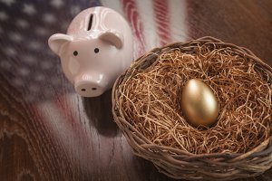 Golden Egg in Nest and Piggy Bank with American Flag Reflection on Wooden Table.