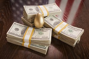 Golden Egg and Thousands of Dollars with American Flag Reflection on Table.