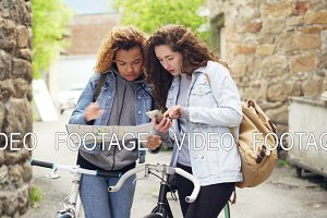 Lost tourists pretty girls are looking at paper map and smartphone screen standing in the street with bicycles and looking for tourist destination.