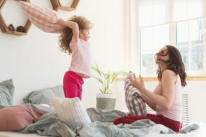 Mother and daughter. Pillow fight