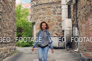 Portrait of charming African American girl walking and dancing looking at camera then posing smiling and touching hair. Happiness, millennials and city life concept.