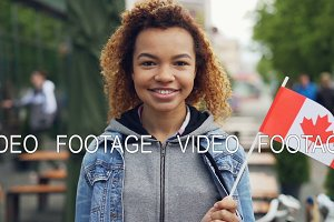 Slowmotion portrait of smiling African American girl traveller holding Canadian flag and looking at camera outdoors. Happy tourist and visiting foreign coutries concept.