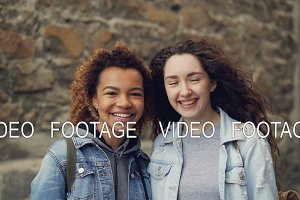 Close-up slowmotion portrait of two happy students African American and Caucasian looking at camera and laughing. Mixed-race friendship and city life concept.