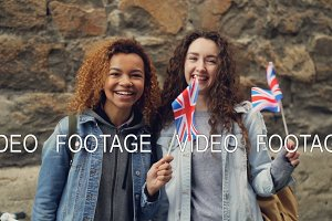 Slowmotion portrait of two female friends foreign students in the UK waving British flags and laughing looking at camera. Friendship, tourism and happy people concept.
