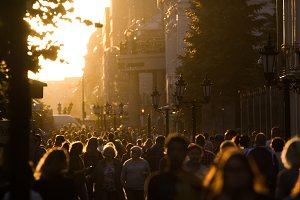 Silhouette crowd of people walking down the pedestrian zone at summer evening sunset