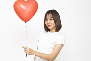 Beautiful Asian woman holding a red heart balloon holding