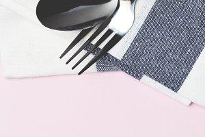 Set table with silver spoon and white napkin on pink
